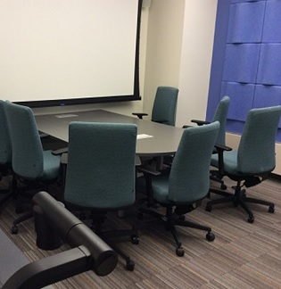 Picture of media room conference table, display screen, et cetera.