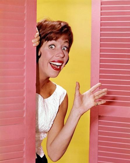 Carol Burnett peeking out of a split doorway waving.