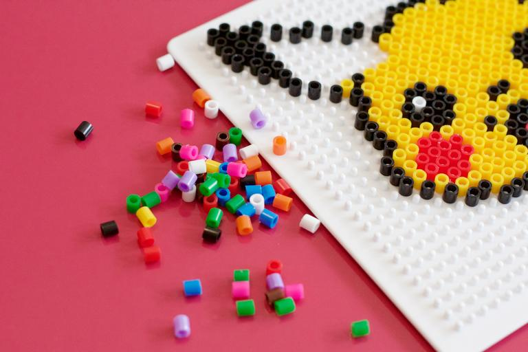 A partial Perler Pikachu and a pile of unused beads