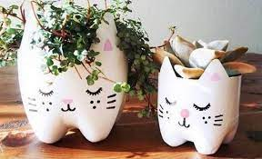 Two planter containers which are painted with cats faces.